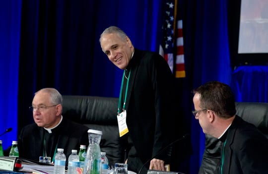 Cardinal Daniel DiNardo of the Archdiocese of Galveston-Houston, center, president of the United States Conference of Catholic Bishops, accompanied by Jose Gomez, archbishop of Los Angeles, left, and Rev. J. Brian Bransfield, right, get a sit before the morning prayer during the United States Conference of Catholic Bishops (USCCB), 2019 Spring meetings in Baltimore, Tuesday, Jun 11, 2019.