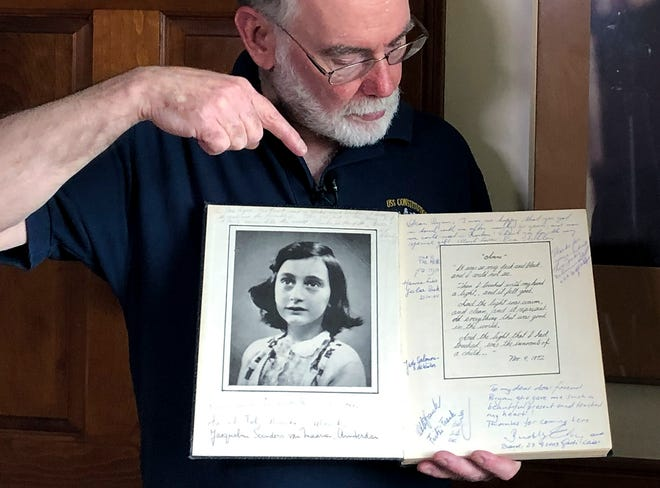Ryan Cooper holds a 1972 portion of a diary that he wrote when he visited Otto Frank. The diary includes a photo of Anne Frank and the autographs of other people he met who knew her.