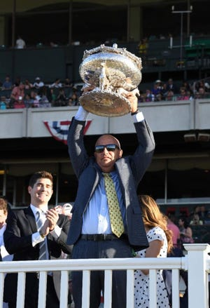 Trainer Mark Casse hoisted the Belmont Stakes trophy after Tracy Farmer's Sir Winston captured the 151st running of the Triple Crown finale.