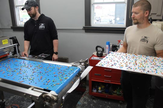 Lab technician Anthony Steinmetz, left, and Christy Machine and Conveyor owner Alex Robinson look over sheets of candy pieces that came out of one of the company's customized ingredient depositor machines. The Fremont business is on Birchard Avenue in the downtown area.
