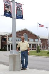 Mayor Rich Harman of Woodville stands by banners honoring local veterans.