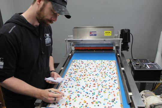 Christy Machine and Conveyor lab technician Anthony Steinmetz counts the number of candy pieces per square that go through one of the Fremont company's food production machines.