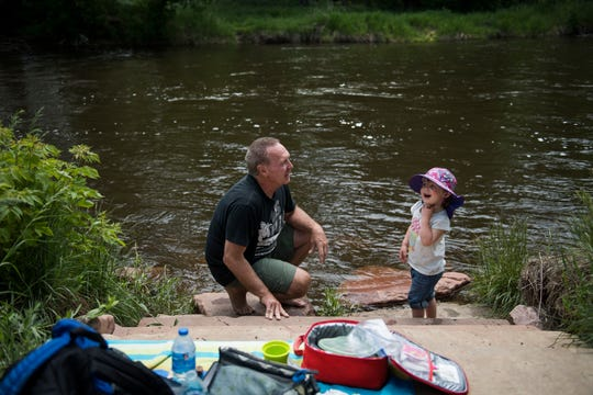 Esmé Haygood hangs out on the bank of the Cache la Poudre River with her babysitter and friend of her parents Bob Mantle on Tuesday, June 11, 2019, at River's Edge Natural Area in Fort Collins, Colo.