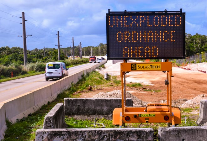 A sign warns motorists that an investigation for unexploded ordnance is being conducted, during roadwork by contract workers, increasing the number of lanes along Route 3 in Dededo on Dec 28, 2018.