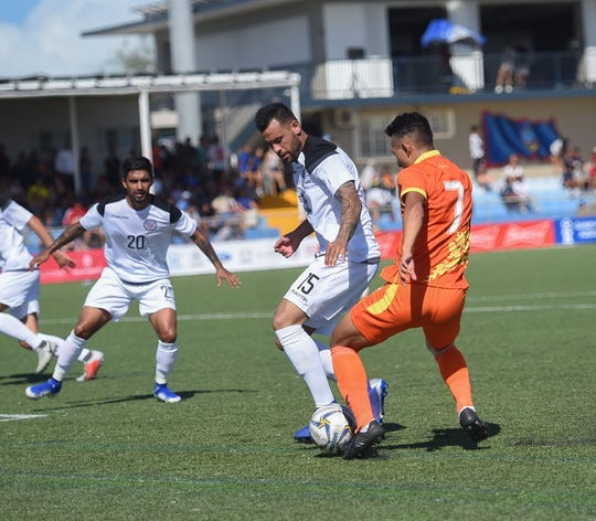 Team Guam's Shawn Nicklaw (15) defends Bhutan's Chencho Gyeltshen (7) during the FIFA World Cup Qatar 2022 and AFC Asian Cup 2023 Preliminary Joint Qualification Round 1 game at the Guam Football Association National Training Center in Dededo June 11.