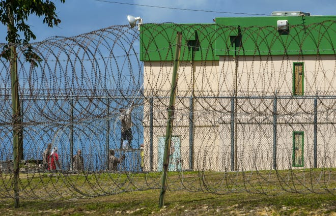 Men be seen painting a building behind multiple rows and coils of razor wire within the Department of Corrections compound in Mangilao in this June 11, 2019, file photo.