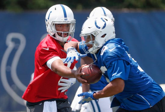 Indianapolis Colts quarterback Jacoby Brissett (7) hands the ball off to running back Jonathan Williams (33) during the Colts mandatory minicamp at the Colts Complex on Tuesday, June 11, 2019.