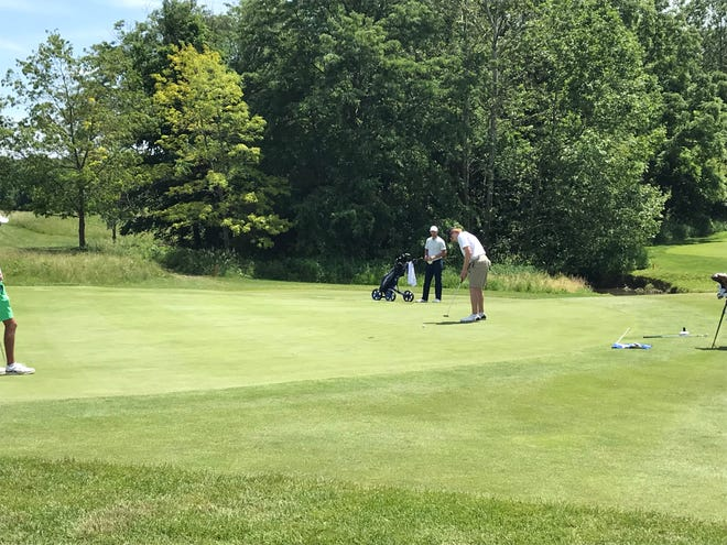 Carmel junior Clay Stirsman putts on the 18th green with Fort Wayne Bishop Dwenger's Jonny Filler watching. Stirsman finished the first round at +2.