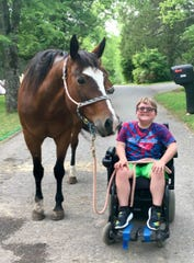 Shining Light Equestrian client Hayden helps out with one of the horses.