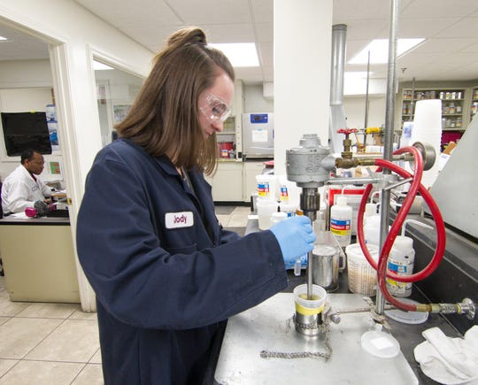 Transtar Autobody Technologies, Inc. is gearing up to expand its Genoa Township headquarters. Helene Seaver, a summer intern at the facility, gets the U.V. visible light transmission of a liquid called a promoter Tuesday, June 11, 2019. A promoter helps paints and other coatings stick to certain materials.