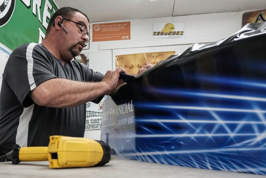 Bruce DeLong, owner of Michigan Graphics & Signs works on wrapping one of many Soap Box Derby cars for the St. Johns Soapbox Derby Thursday, May 23, 2019.