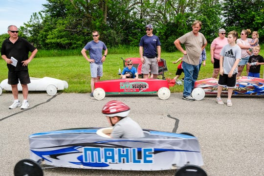 People watch as a Soap Box Derby racer speeds down the ramp during a practice Saturday, June 8, 2019.