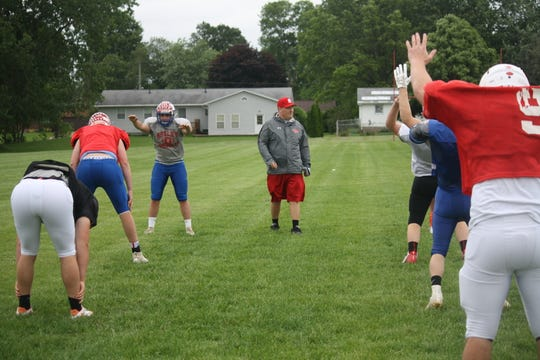 New Shelby football coach Rob Mahaney puts his North all-stars through some stretching exercises at the start of practice on Monday.