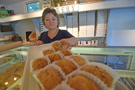 Darlene Mast, owner of Share N' Dipity, arranges baked goods at her store at 287 Taylor Road in Mansfield.