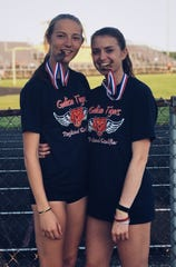Kerrigan Myers (left) and Marisa Gwinner chomping down on some of the medals they amassed as teammates for the Galion Tigers.