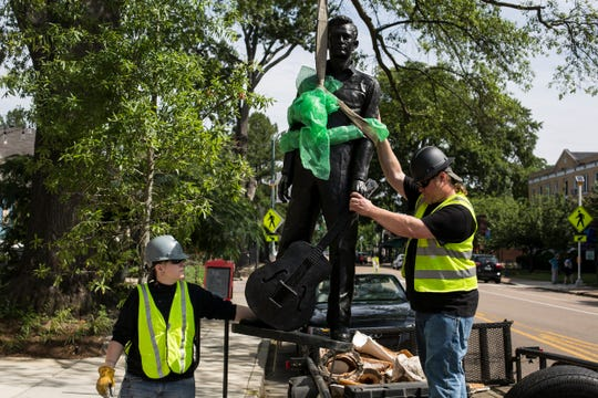 Wendy Young, left, and Geordan Lugar, with Lugar Foundry and Fabrication, help move a life-sized statue of Johnny Cash into position outside 999 S. Cooper St. in Memphis on June 11, 2019. The statue was sculpted by Memphis artist Mike McCarthy and will be officially unveiled to the public at 5 p.m. Wednesday near the site of the singer's first public performance at Galloway United Methodist Church.