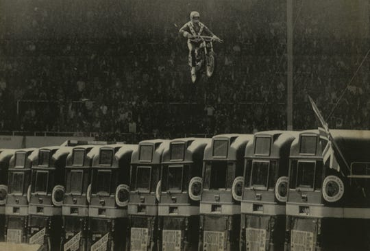 "Stuntman Evel Knievel leaps over 13 parked buses at Wembley Stadium in London on May 26, 1975. (After clearing the buses, Knievel crashed on landing and was taken to a hospital.) The Harley he wrote is part of a new exhibit at the Harley-Davidson Museum, ""Daredevils."""