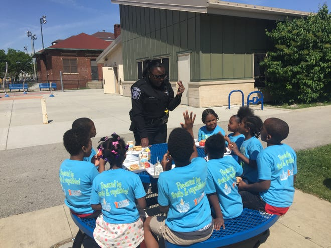 Deputy Sheriff Cassandra Joshua talks with students from Auer Avenue School over breakfast at the kickoff of Milwaukee's summer meal program on Tuesday.
