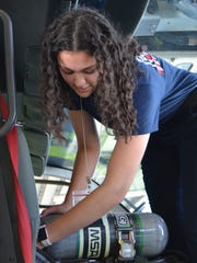 Kylie Miller, a recent graduate of Ronald Reagan High School, tests equipment at Milwaukee Mitchell International Airport's Fire and Rescue.