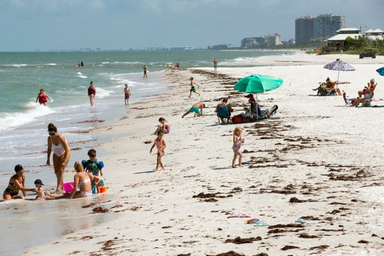 Beach goers enjoy playing along the shore at Clam Pass beach, Tuesday, June 11, 2019, in Naples.