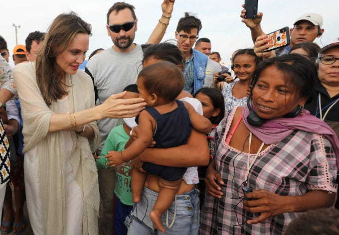 UNHCR's special envoy Angelina Jolie caresses a baby as she meets Venezuelan migrants at an United Nations-run camp in Maicao, Colombia, on border with Venezuela, Saturday, June 8, 2019. Jolie visited the camp to learn more about the conditions faced by migrants and refugees and raise awareness about their needs.