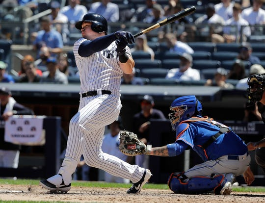New York Yankees' Luke Voit follows through on a three-run home run as New York Mets catcher Tomas Nido, right, watches during the fourth inning in the first baseball game of a doubleheader, Tuesday, June 11, 2019, in New York. (AP Photo/Frank Franklin II)