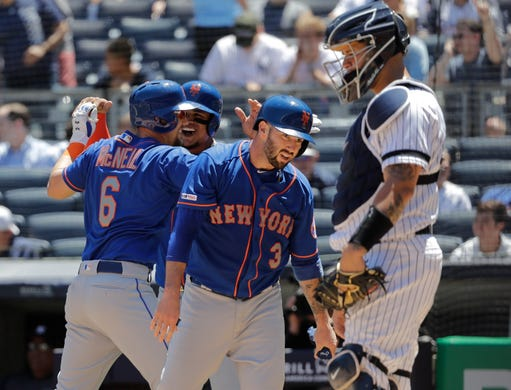 New York Yankees catcher Gary Sanchez, right, looks away as New York Mets' Jeff McNeil (6) celebrates with teammates Tomas Nido (3) and Juan Lagares after McNeil hit a three-run home run during the third inning in the first baseball game of a doubleheader Tuesday, June 11, 2019, in New York. (AP Photo/Frank Franklin II)