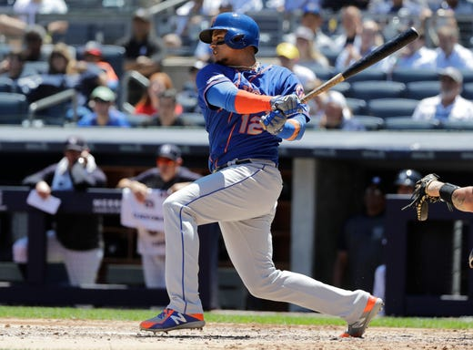 New York Mets' Juan Lagares (12) hits an RBI single against the New York Yankees during the third inning in the first baseball game of a doubleheader, Tuesday, June 11, 2019, in New York. (AP Photo/Frank Franklin II)
