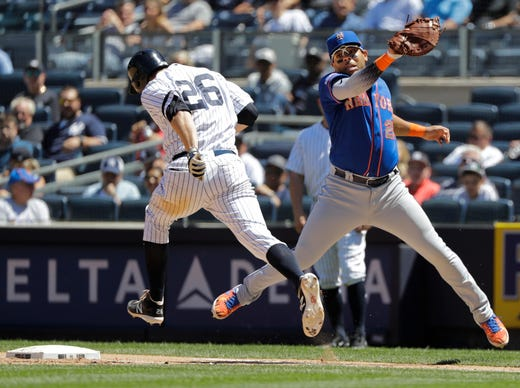 New York Yankees' DJ LeMahieu (26) runs past New York Mets first baseman Dominic Smith (22) to reach first base on a throwing error by Todd Frazier during the fourth inning in the first baseball game of a doubleheader, Tuesday, June 11, 2019, in New York. (AP Photo/Frank Franklin II)