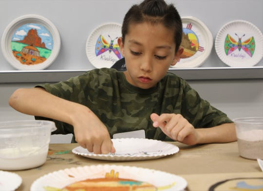 Ezekiel Webber works on a sandpainting in class offered at Dahayoigii A Youth Art Event on June 11 at San Juan College in Farmington.