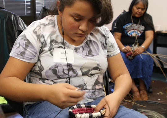 Nizhoni Louie-Bull works on a Navajo wedding basket during a class at Dahayoigii A Youth Art Event on June 11 at San Juan College in Farmington.