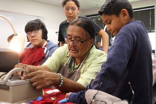 Jesse Monongya, center, demonstrates how to cut stone during the jewelry class at Dahayoigii A Youth Art Event on June 11 at San Juan College in Farmington.