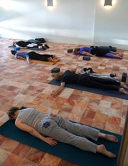A class at Breathe Yoga + Salt takes a class in a room tiled in Himalayan salt.