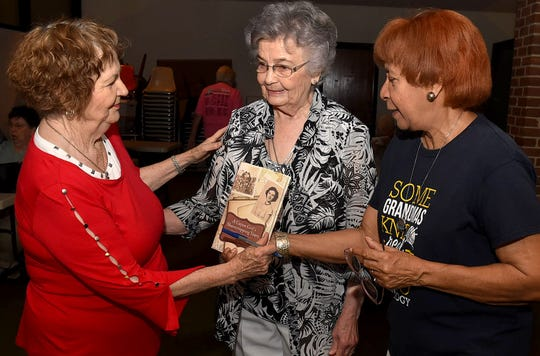 Viola Fontenot presents Sylvia Morel with an autographed copy of her book with Etha Amling looking on.