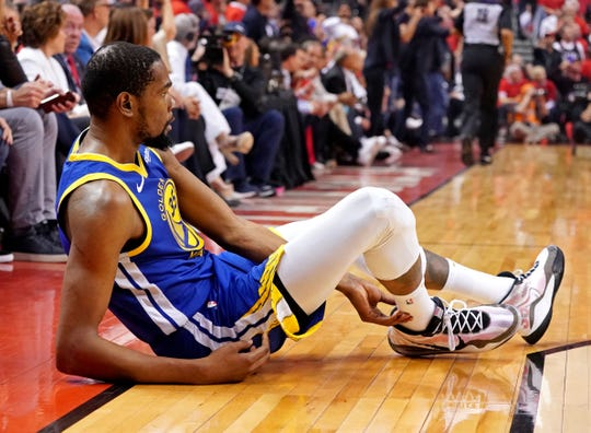 Jun 10, 2019: Golden State Warriors forward Kevin Durant (35) sits on the court after an apparent injury during the second quarter in game five against the Toronto Raptors of the 2019 NBA Finals at Scotiabank Arena.