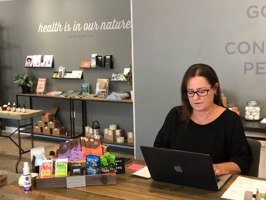 Kaya Hemp Co. owner Cathleen Mitchell sits in the recently-opened brick-and-mortar location of her business.