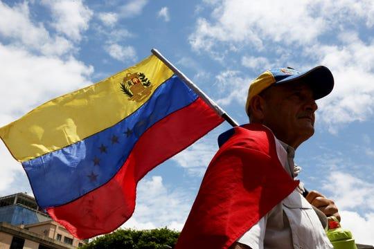 Un hombre con bandera de Venezuela en mano protesta contra el gobierno de Nicolás Maduro.