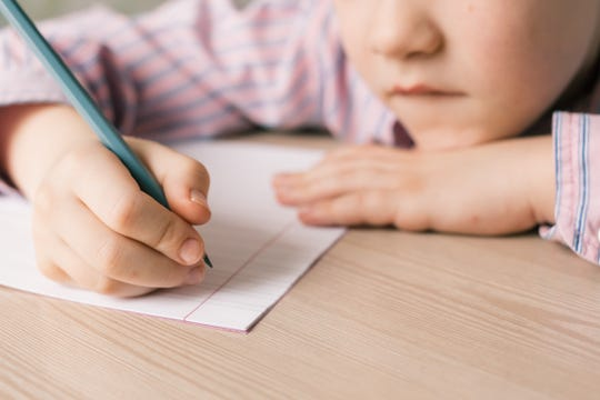 A child prepares to write on a piece of notebook paper.