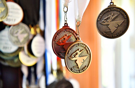 "Medals won by John Barton, 93, and his wife Norma, 94, from their years of competition in the York County Senior Games are shown at the Barton home in Stewartstown, Tuesday, June 11, 2019. John, who will be the torch-bearer for the 2019 opening ceremonies, has participated in the games since 2007. Norma was able to participate for about five of those years and both recall her as being known as the, ""bocce queen."" Dawn J. Sagert photo"