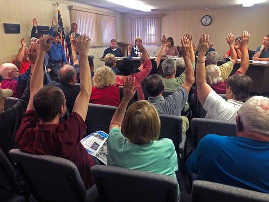 Audience members at Monday night's Cambridge City Town Council meeting raise their hands to signal their opposition to a proposed reconfiguration of U.S. 40 running through the town.