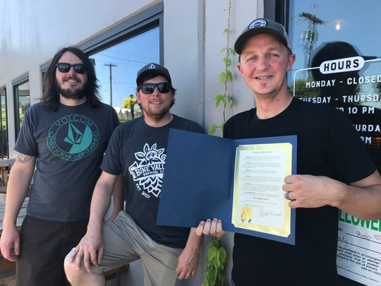 Donny Raisanen (left) and Jim Weinman (center) of Bine Valley Brewing and Jake Bonham (right) of Salem Ale Works pictured at Salem Ale Works with the Salem Brewery District proclamation on June 11, 2019.