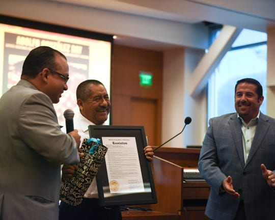 Adolfo González (center) accepts a resolution from Monterey County Supervisor Luis Alejo (left).