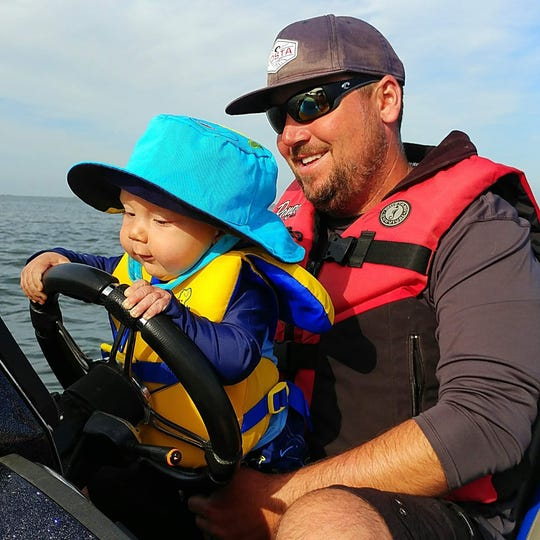 Jason Borofka helps his son, J.T. Borofka, drive the boat.