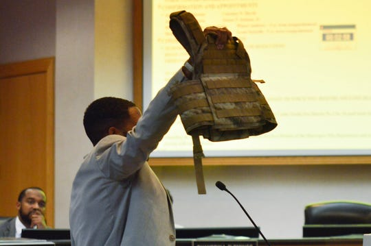A citizen holds up a bullet-proof vest during the Shreveport city council meeting on Tuesday, June 11, during a discussion about the sagging pants ordinance.