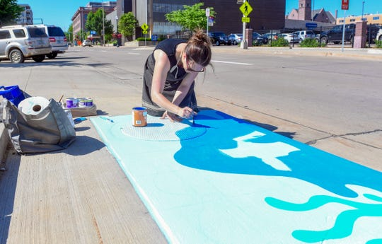 Ashton Dockendorf, local artist, paints a storm drain on Dakota Avenue on Friday, June 7, in downtown Sioux Falls.