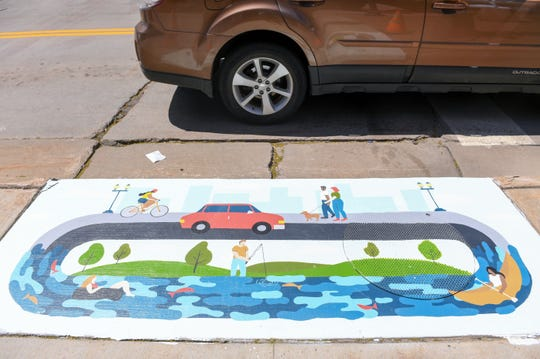 Traffic passes a completed storm drain painting in downtown Sioux Falls.