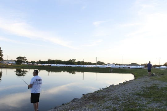 Scotty Slavens and his son Isaac, 10, fish in the pond at Nelson Park on Monday. The Lebanon City Council agreed to sell the park to White River Marine Group, whose Tracker boats sit in storage in the background, in a special meeting June 3, prompting protest from some residents.