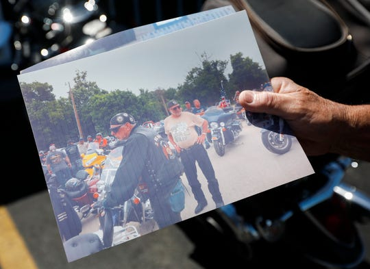 Mike Howard holds a picture of his friend Bill Maxheimer, center. Maxheimer, a Marine veteran and Purple Heart recipient, died Sunday due to injuries from a motorcycle accident.