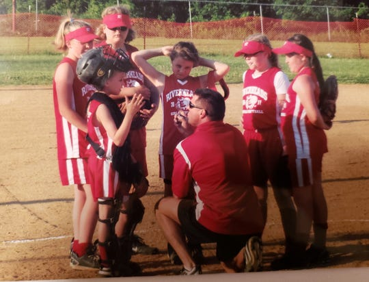 Youth Riverheads softball players huddled around coach Mike Walters, who now coaches several of the players at the high school level. Among the players in the photo are Sara Moore (in catcher's gear), Emily Walters to Moore's left, and Faith Christian in center.