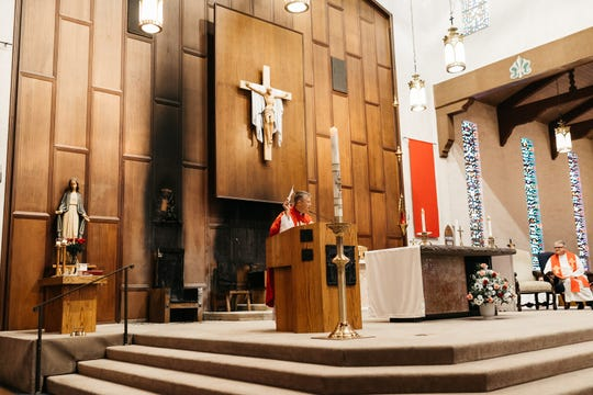 Father Timothy Holeda, parochial vicar at Co-Cathedral of St. Thomas More, speaks during mass on Sunday, June 9, several days after an intentionally set fire damaged the main sanctuary.